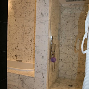 Modelo de cuarto de baño principal, asiático, de tamaño medio, con armarios con paneles lisos, puertas de armario de madera oscura, ducha empotrada, sanitario de pared, baldosas y/o azulejos blancas y negros, baldosas y/o azulejos de mármol, paredes blancas, suelo de mármol, lavabo de seno grande, encimera de mármol, suelo blanco y ducha con puerta con bisagras