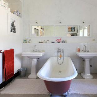Immagine di una stanza da bagno padronale mediterranea con vasca freestanding, piastrelle bianche, pareti bianche, pavimento in cemento, lavabo a colonna e pavimento grigio