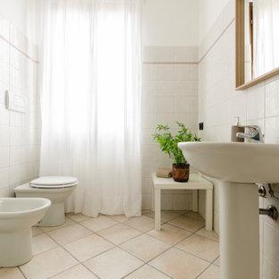 Immagine di una stanza da bagno mediterranea di medie dimensioni con piastrelle bianche, pareti bianche, lavabo a colonna e pavimento beige