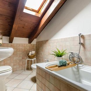 Immagine di una stanza da bagno mediterranea di medie dimensioni con vasca da incasso, bidè, piastrelle beige, pareti bianche, lavabo a colonna e pavimento beige