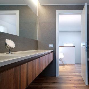 Ispirazione per una stanza da bagno contemporanea di medie dimensioni con ante lisce, ante in legno scuro, pareti grigie, pavimento in legno massello medio, lavabo integrato e top in marmo