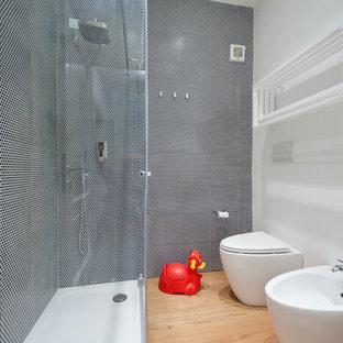 Esempio di una piccola stanza da bagno con doccia minimal con doccia ad angolo, bidè, pistrelle in bianco e nero, piastrelle in ceramica, pareti bianche e parquet chiaro