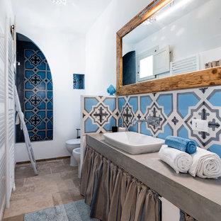 Esempio di una stanza da bagno con doccia mediterranea con nessun'anta, doccia alcova, WC monopezzo, piastrelle blu, pareti bianche, lavabo da incasso, top in cemento, pavimento beige, doccia aperta e top grigio