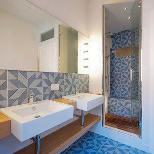 Esempio di una stanza da bagno con doccia stile marinaro di medie dimensioni con ante in legno chiaro, doccia alcova, piastrelle multicolore, piastrelle in ceramica, pareti bianche, pavimento con piastrelle in ceramica, lavabo rettangolare, top in legno e porta doccia a battente