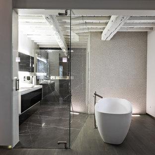 Foto de cuarto de baño principal, contemporáneo, grande, con armarios con paneles lisos, puertas de armario negras, bañera exenta, combinación de ducha y bañera, paredes grises, suelo de madera pintada, lavabo de seno grande y suelo negro