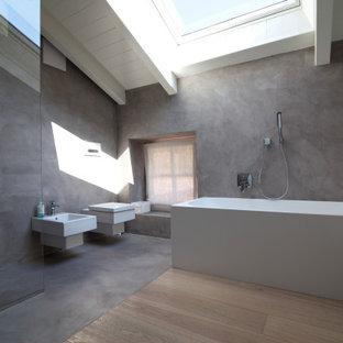 Inspiration för mellanstora moderna vitt en-suite badrum, med släta luckor, vita skåp, ett badkar i en alkov, en kantlös dusch, en vägghängd toalettstol, grå väggar, ett väggmonterat handfat, bänkskiva i akrylsten och med dusch som är öppen
