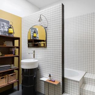 Ispirazione per una stanza da bagno industriale di medie dimensioni con ante nere, vasca da incasso, piastrelle bianche, piastrelle in ceramica, pareti bianche, pavimento in cemento, lavabo a colonna e pavimento grigio