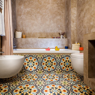 Modelo de cuarto de baño infantil, mediterráneo, de tamaño medio, con bañera empotrada, combinación de ducha y bañera, bidé, paredes beige, suelo de baldosas de cerámica, suelo multicolor y ducha con cortina