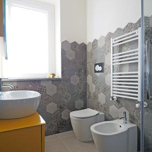 Modelo de cuarto de baño contemporáneo, pequeño, con armarios con paneles lisos, puertas de armario amarillas, bidé, baldosas y/o azulejos grises, baldosas y/o azulejos de porcelana, paredes blancas, suelo de baldosas de porcelana, lavabo sobreencimera, suelo gris y encimeras amarillas