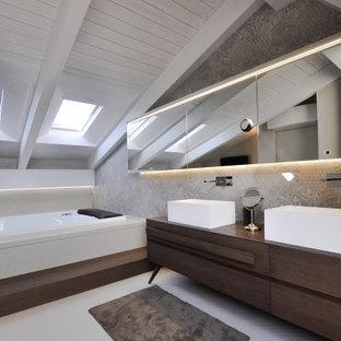 Modernes Badezimmer En Suite mit flächenbündigen Schrankfronten, dunklen Holzschränken, Einbaubadewanne, grauen Fliesen, grauer Wandfarbe, Aufsatzwaschbecken, Waschtisch aus Holz, grauem Boden, brauner Waschtischplatte, Doppelwaschbecken, freistehendem Waschtisch und Holzdielendecke in Bologna