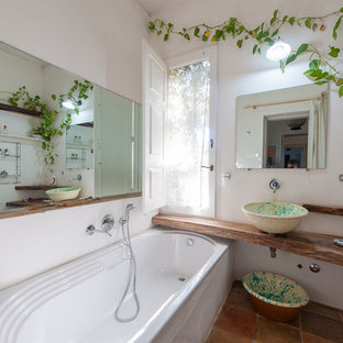Example of a tuscan master orange tile, brown tile and terra-cotta tile terra-cotta floor and brown floor drop-in bathtub design in Bari with open cabinets, white walls, a vessel sink, wood countertops and brown countertops