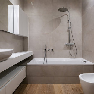 Mid-sized modern master bathroom in Milan with flat-panel cabinets, white cabinets, porcelain tile, a vessel sink, an alcove tub, a shower/bathtub combo, a bidet, gray tile, grey walls, medium hardwood floors, brown floor, an open shower and white benchtops.