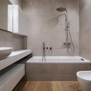 Идея дизайна: главная ванная комната среднего размера в стиле модернизм с плоскими фасадами, белыми фасадами, керамогранитной плиткой, настольной раковиной, ванной в нише, душем над ванной, биде, серой плиткой, серыми стенами, паркетным полом среднего тона, коричневым полом, открытым душем и белой столешницей