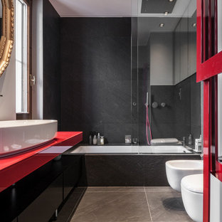 Photo of a contemporary master bathroom in Milan with ceramic floors, a vessel sink, glass benchtops, flat-panel cabinets, black cabinets, an undermount tub, a shower/bathtub combo, a bidet, black tile, grey floor, a sliding shower screen and red benchtops.