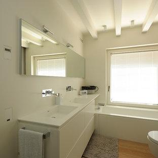 Modelo de cuarto de baño principal, contemporáneo, pequeño, con armarios con paneles lisos, bañera encastrada, sanitario de pared, paredes blancas, suelo de madera en tonos medios y lavabo integrado