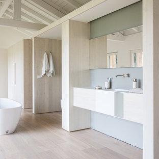 Idee per una grande stanza da bagno padronale minimalista con ante lisce, ante in legno chiaro, vasca freestanding, pareti grigie, parquet chiaro e lavabo sospeso