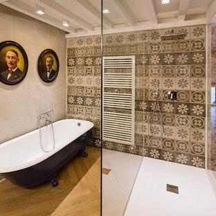 Idee per una stanza da bagno padronale eclettica con vasca con piedi a zampa di leone, doccia aperta, piastrelle in ceramica, pareti grigie, parquet chiaro e doccia aperta