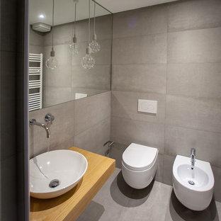 Idee per una stanza da bagno design con WC sospeso, piastrelle grigie, pareti grigie, lavabo a bacinella, top in legno, pavimento grigio e top marrone
