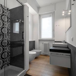 Esempio di una stanza da bagno con doccia design di medie dimensioni con ante bianche, doccia ad angolo, WC sospeso, pistrelle in bianco e nero, piastrelle in ceramica, pareti bianche, parquet chiaro, lavabo rettangolare e porta doccia scorrevole