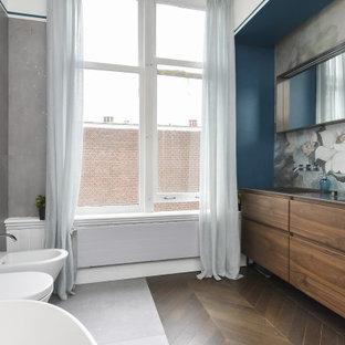 ローマのコンテンポラリースタイルのおしゃれなマスターバスルーム (フラットパネル扉のキャビネット、中間色木目調キャビネット、置き型浴槽、壁掛け式トイレ、セメントタイル、マルチカラーの壁、木目調タイルの床、アンダーカウンター洗面器、茶色い床、黒い洗面カウンター、洗面台1つ、フローティング洗面台、壁紙) の写真