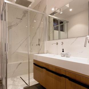 Идея дизайна: ванная комната среднего размера в стиле модернизм с фасадами с декоративным кантом, светлыми деревянными фасадами, душем без бортиков, раздельным унитазом, белой плиткой, мраморной плиткой, белыми стенами, полом из керамогранита, душевой кабиной, подвесной раковиной, столешницей из искусственного камня, коричневым полом, душем с раздвижными дверями, белой столешницей, сиденьем для душа, тумбой под две раковины, подвесной тумбой и многоуровневым потолком