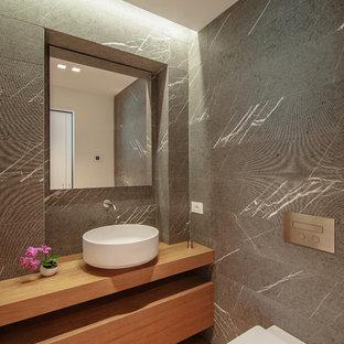 Idee per una stanza da bagno contemporanea con top in legno, WC sospeso, piastrelle grigie, lavabo a bacinella, ante in legno scuro e top marrone