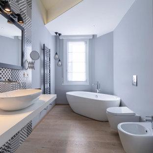 Immagine di una stanza da bagno padronale design di medie dimensioni con vasca freestanding, WC sospeso, pistrelle in bianco e nero, piastrelle in gres porcellanato, pareti grigie, parquet chiaro, lavabo a bacinella, un lavabo, mobile bagno sospeso e soffitto ribassato