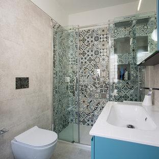 Foto di una piccola stanza da bagno padronale stile marino con ante lisce, ante blu, doccia alcova, WC sospeso, piastrelle multicolore, piastrelle in ceramica, pareti beige, lavabo integrato e porta doccia scorrevole