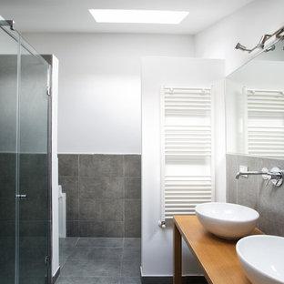 Immagine di una stanza da bagno minimal di medie dimensioni con piastrelle grigie, piastrelle in gres porcellanato, pareti bianche, pavimento in gres porcellanato, lavabo a bacinella, top in legno e pavimento grigio