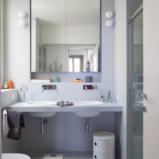 Immagine di una stanza da bagno padronale minimal di medie dimensioni con doccia alcova, WC sospeso, piastrelle grigie, piastrelle in gres porcellanato, pareti grigie, pavimento in gres porcellanato, lavabo da incasso, pavimento grigio, top grigio, due lavabi e porta doccia a battente