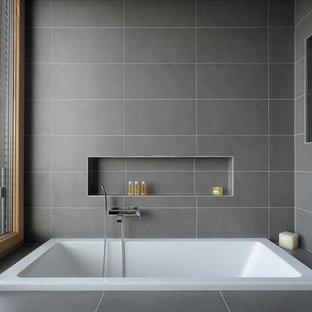 Esempio di una grande stanza da bagno padronale contemporanea con vasca da incasso, piastrelle grigie e pavimento con piastrelle in ceramica
