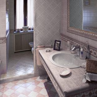 Imagen de cuarto de baño principal, moderno, de tamaño medio, con bañera empotrada, sanitario de dos piezas, baldosas y/o azulejos rosa, baldosas y/o azulejos de cerámica, paredes grises, suelo de baldosas de cerámica, lavabo encastrado y encimera de piedra caliza
