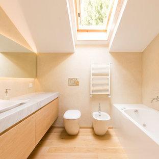 Design ideas for a scandinavian bathroom in Milan with flat-panel cabinets, light wood cabinets, a bidet, beige walls, light hardwood floors and a vessel sink.