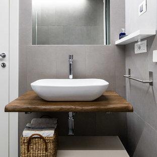 Esempio di una stanza da bagno con doccia nordica con ante lisce, ante beige, piastrelle grigie, lavabo a bacinella, top in legno, pavimento grigio e top marrone