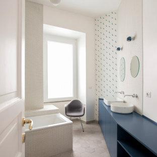 Modelo de cuarto de baño principal, actual, de tamaño medio, con armarios con paneles lisos, puertas de armario azules, bañera encastrada, baldosas y/o azulejos blancos, baldosas y/o azulejos de porcelana, paredes blancas, suelo de baldosas de porcelana, lavabo sobreencimera, suelo beige y encimeras azules