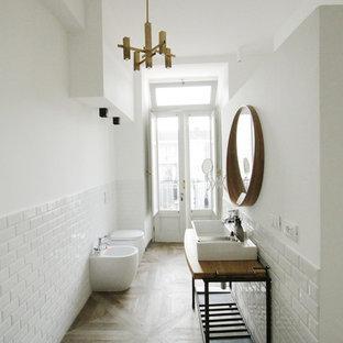 Cette photo montre une très grand salle d'eau industrielle avec un placard à porte plane, des portes de placard blanches, une douche à l'italienne, un WC à poser, un carrelage blanc, des carreaux de porcelaine, un mur blanc, un sol en carrelage de porcelaine, un plan de toilette en bois, un sol marron, aucune cabine, un plan vasque et un plan de toilette marron.