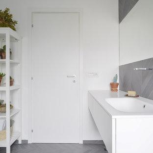 Immagine di una stanza da bagno minimal con ante bianche, piastrelle grigie, pareti bianche, top bianco, ante lisce, lavabo integrato e pavimento grigio