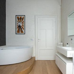 Imagen de cuarto de baño actual con armarios con paneles lisos, puertas de armario blancas, bañera esquinera, paredes blancas, suelo de madera clara, lavabo suspendido, suelo marrón y encimeras blancas