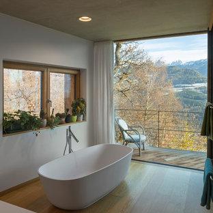 Immagine di una stanza da bagno design con vasca freestanding, pareti bianche e pavimento in legno massello medio