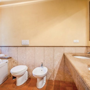 Esempio di una stanza da bagno padronale country di medie dimensioni con vasca idromassaggio, vasca/doccia, WC a due pezzi, piastrelle beige, piastrelle di marmo, pavimento in terracotta, lavabo a bacinella, top in marmo, pavimento rosso, porta doccia scorrevole e top beige
