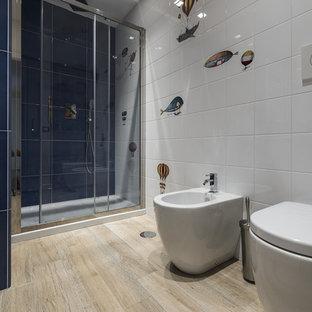 Modelo de cuarto de baño infantil, contemporáneo, con armarios con paneles lisos, puertas de armario azules, ducha empotrada, bidé, baldosas y/o azulejos blancos, suelo de madera clara, suelo beige, ducha con puerta corredera y encimeras blancas