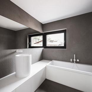 Imagen de cuarto de baño minimalista con armarios con paneles lisos, puertas de armario blancas, bañera encastrada, paredes grises, suelo de baldosas de porcelana, encimera de laminado y lavabo sobreencimera