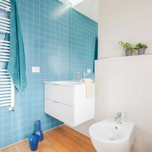 Immagine di una piccola stanza da bagno contemporanea con ante lisce, ante bianche, bidè, piastrelle blu e parquet chiaro