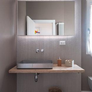 Ispirazione per una stanza da bagno design con WC sospeso, piastrelle grigie, pareti grigie, lavabo a bacinella, top in legno, pavimento grigio e top beige