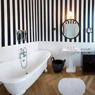 Klassisk inredning av ett badrum, med ett piedestal handfat, flerfärgade väggar, ljust trägolv och ett badkar med tassar