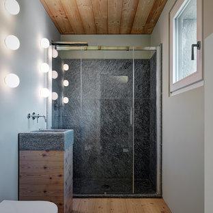 Immagine di una piccola stanza da bagno con doccia contemporanea con ante lisce, doccia alcova, pareti grigie, porta doccia scorrevole, ante in legno chiaro, WC sospeso, piastrelle grigie e parquet chiaro