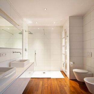 Ejemplo de cuarto de baño con ducha, actual, grande, con armarios con paneles lisos, puertas de armario blancas, ducha a ras de suelo, baldosas y/o azulejos blancos, suelo de madera en tonos medios, sanitario de pared y lavabo sobreencimera