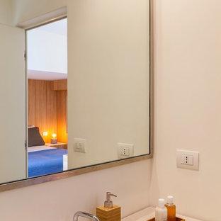 Ejemplo de cuarto de baño con ducha, moderno, de tamaño medio, con armarios abiertos, ducha a ras de suelo, sanitario de dos piezas, baldosas y/o azulejos con efecto espejo, paredes beige, suelo de cemento, lavabo sobreencimera, encimera de cemento, suelo gris, ducha con puerta con bisagras y encimeras blancas