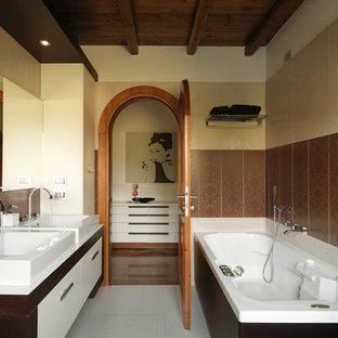 Imagen de cuarto de baño principal, contemporáneo, con lavabo sobreencimera, armarios con paneles lisos, puertas de armario blancas, bañera empotrada y baldosas y/o azulejos beige