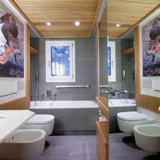 Imagen de cuarto de baño principal, rústico, pequeño, con puertas de armario de madera clara, bañera encastrada, sanitario de pared, baldosas y/o azulejos grises, baldosas y/o azulejos de piedra, paredes blancas, suelo de baldosas de porcelana, lavabo suspendido, encimera de vidrio, suelo gris y ducha con puerta corredera